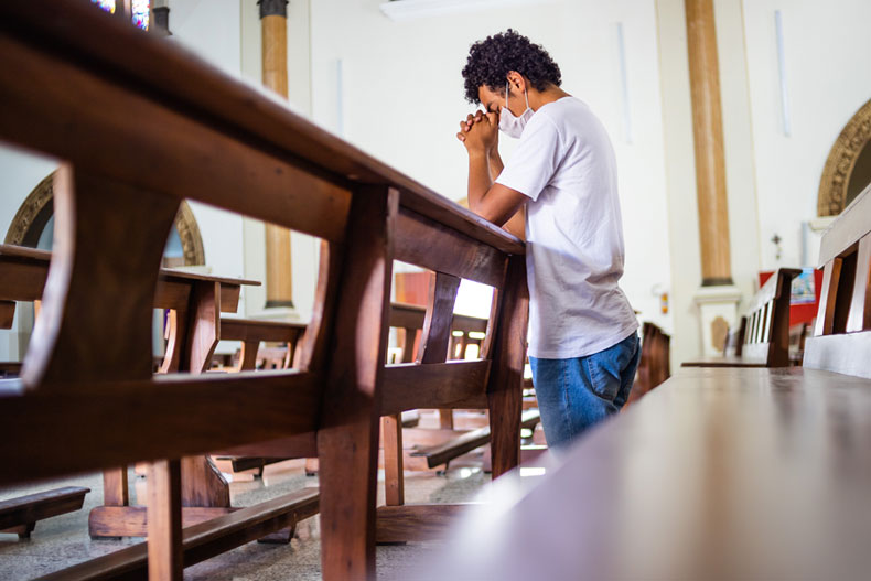 A young man kneels in prayer in an empty church pew