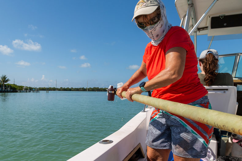 Kathleen Sullivan Sealey guides a long fiberglass tube holding clear plastic sample bottles over the edge of an open fisherman boat in the Florida Keys. Photos: Janette Neuwahl Tannen/University of Miami