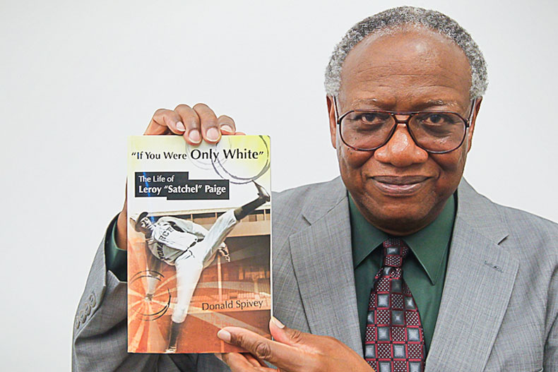 """Donald Spivey photographed with his book, """"If You Were Only White: The Life of Leroy 'Satchel' Paige"""""""