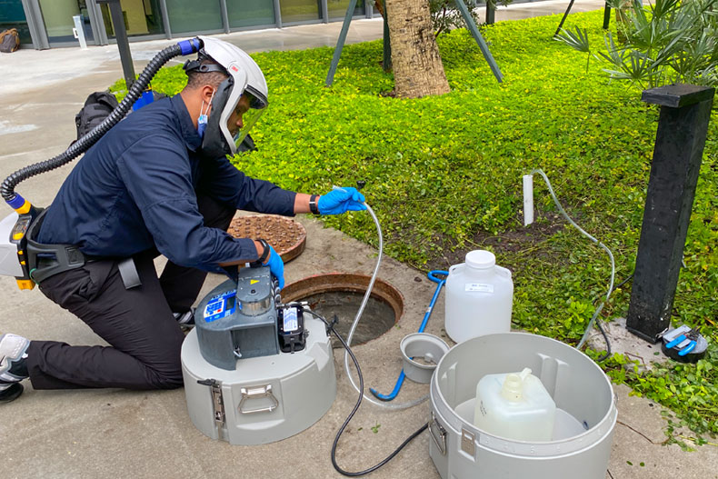 Walter Lamar, executive director of Facilities, Safety and Compliance for the Miller School of Medicine setting up an autosampler device to collect wastewater outside the Lakeside Village residential hall.