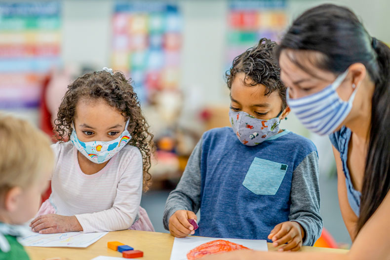Multi-ethnic group of children coloring at a table while wearing protective face masks to avoid the transfer of germs.